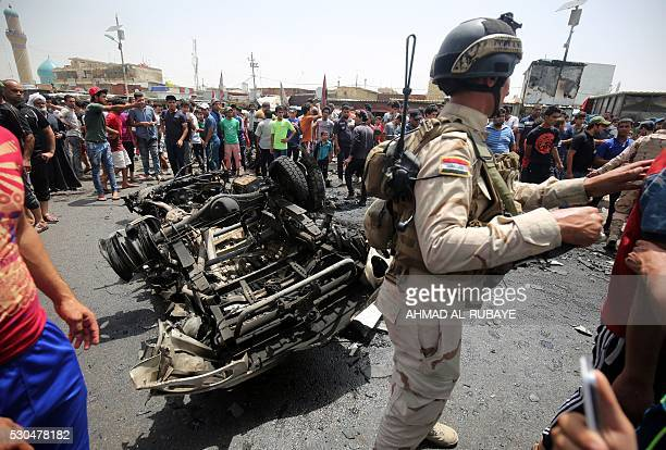 A member of the Iraqi security forces stands guard as civilians look at the damage following a car bomb attack in Sadr City a Shiite area north of...