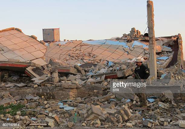 A member of the Iraqi security forces stands in the rubble of destroyed buildings in the rural Husayba alSharkiya area east of Anbar province's...