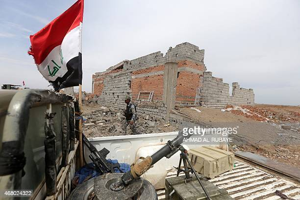 A member of the Iraqi security forces walks past a damaged house in the southern entrance of the city of Tikrit on March 29 2015 during a military...