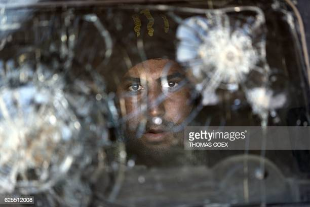 A member of the Iraqi Special Forces is seen behind the reinforced windshield of an Iraqi Special Forces armoured vehicle bearing the bullet marks in...
