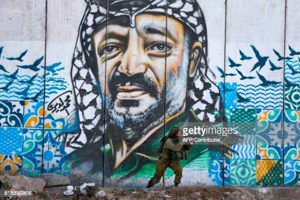 TOPSHOT A member of the Israeli border guards looks through the scope of an assault rifle as he stands by a mural showing a graffiti image of late...