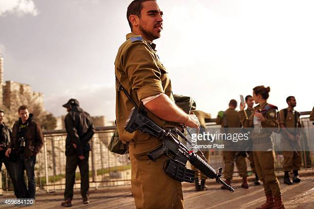 A member of the Israeli Defense Forces pauses in a park near the Old City on November 28 2014 in Jerusalem Israel Nine Israelis have been killed in a...
