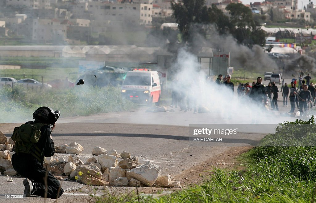A member of the Israeli security forces fires a tear gas canister towards Palestinian protestors during clashes at the entrance of the Jalama checkpoint, near the West Bank city of Jenin, on February 15, 2013. AFP PHOTO/SAIF DAHLAH