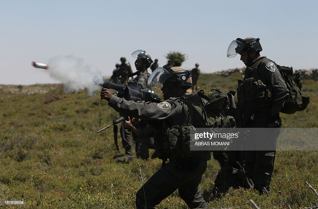 A member of the Israeli security forces fires a tear gas canister during clashes with demonstrators from the West Bank village of Deir Jarir, northeast of Ramallah, following a march against construction on their land by members of the nearby Jewish settlement of Ofra on April 26, 2013.