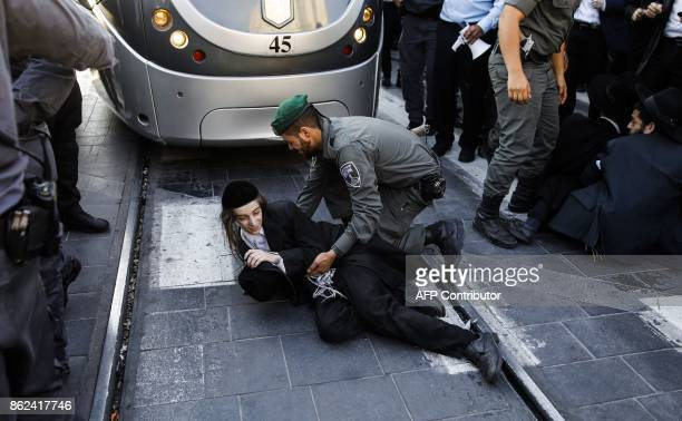 A member of the Israeli security forces grabs an UltraOrthodox Jewish boy demonstrator blocking a main road while dispersing a protest against...