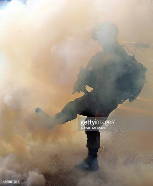 A member of the Israeli security forces kicks a tear gas canister during clashes with Palestinian protesters on the highway between Jerusalem and...