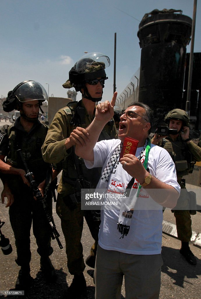 A member of the Israeli security forces restrains a journalist as he shout slogans and holds an international press card in his hand, during a demonstration demanding for the free movement of journalists and Palestinians at the Qalandia checkpoint between Ramallah and Jerusalem, in the occupied West Bank on July 17, 2013.