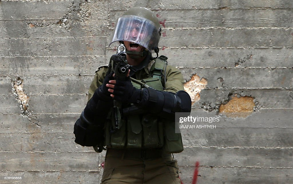 A member of the Israeli security forces shouts during clashes with Palestinian protesters following a weekly demonstration against the expropriation of Palestinian land by Israel in the village of Kfar Qaddum, near Nablus, in the occupied West Bank, on May 6, 2016. / AFP / JAAFAR