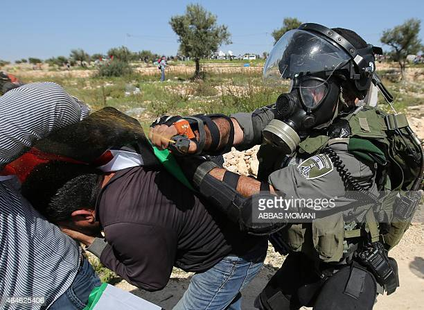 A member of the Israeli security forces sprays pepper spray as he detains a Palestinian protester during clashes on February 27 2015 following a...