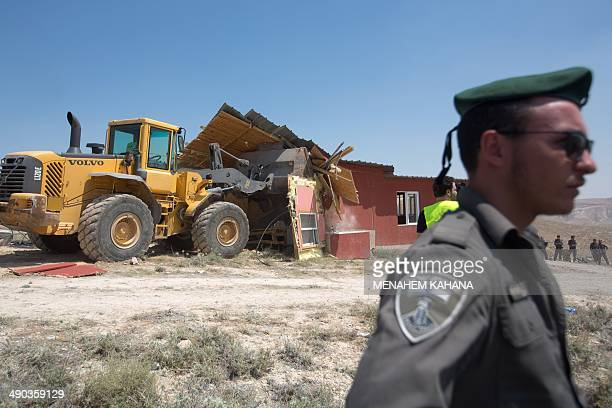 A member of the Israeli security forces stands guard as an Israeli army bulldozer demolishes an illegal house in the West Bank settlement of Maale...