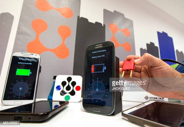 A member of the Israeli startup StoreDot demonstrates a bioorganic charger system which they are developing that can recharge a smartphone battery in...