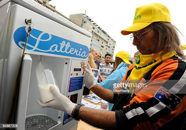 A member of the Italian Agricultural Producers Association pours free bottles of milk to give to passersby in protest of milk prices in Milan Italy...