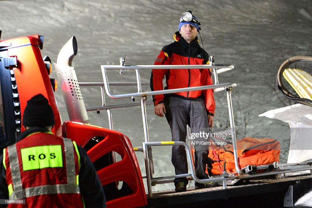 A member of the Italian Alpine rescue team stands near the body of one of the six Russian tourists who died after an accident in Mount Cermis, near Cavalese in Val di Fiemme, on January 5, 2013. A snowmobile accident in the Italian Alps left six tourists dead and two others seriously injured. The eight -- all from eastern Europe, or Russia -- were riding on the vehicle across an unlit slope on Mount Cermis in the Trento region, rescuers said. Mount Cermis was the scene of two deadly cable car accidents in 1976 and 1998. In the latter a US military plane cut a cable supporting a gondola of an aerial tramway. AFP PHOTO / GIUSEPPE CACACE