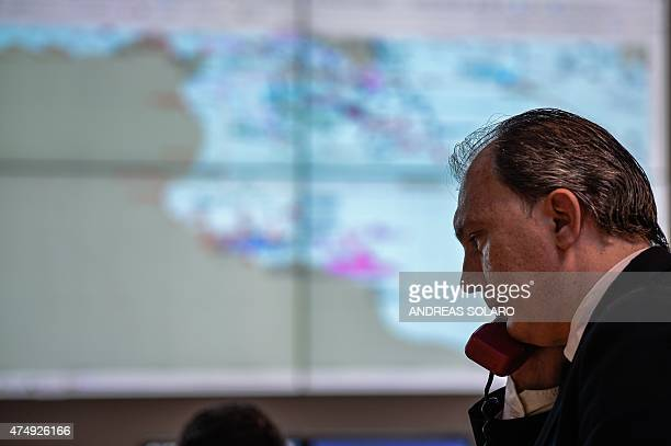 A member of the Italian Coast Guard speaks on the phone as he monitors the movement of shipping traffic in the Mediterranean Sea off the Italian...