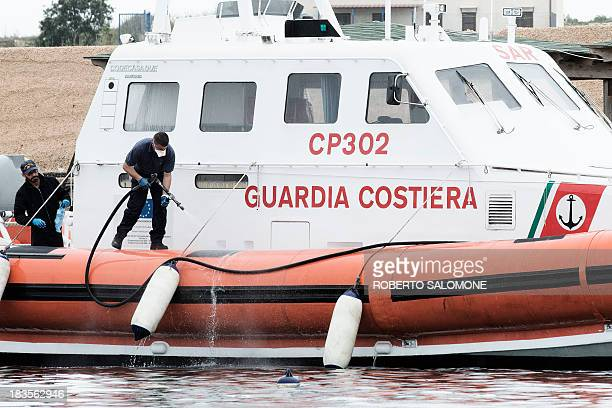 A member of the Italian Coast Guard washes his boat after the disembarkation of the bodies of migrants who were killed in a shipwreck off the Italian...