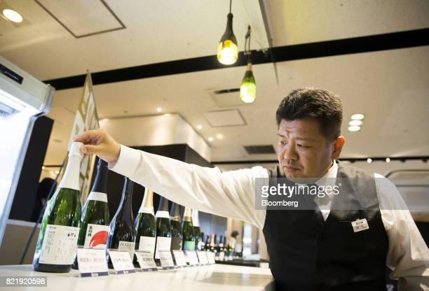A member of the Japan Awasake Association displays bottles of sparkling sake including the NanbuBijin Awasake Sparkling brewed by NanbuBijin Co left...