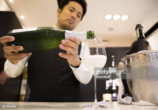 A member of the Japan Awasake Association pours a glass of Nanbu Bijin Asa Wake Sparkling sake brewed by Nanbu Bijin Co during a Sake Marche event at...