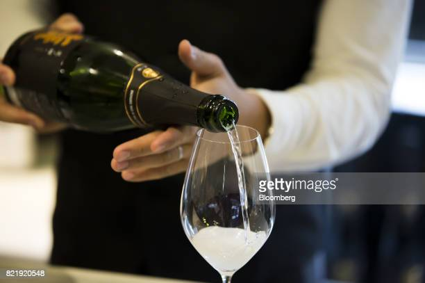 A member of the Japan Awasake Association pours a glass of sparkling sake at the association's booth during a Sake Marche event at the Isetan...