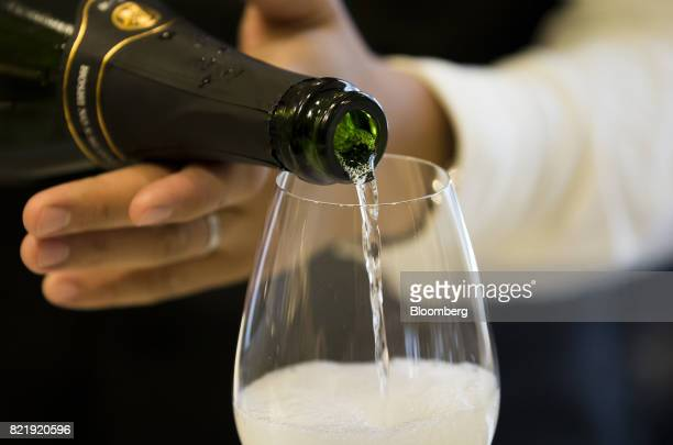 A member of the Japan Awasake Association pours a glass of sparkling sake at the association's booth during a Sake Marche event held at the Isetan...