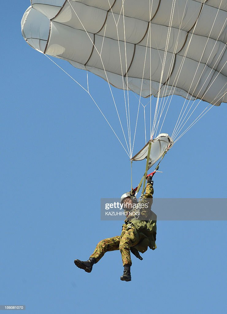 A member of the Japanese Self Defense Forces ground troops parachutes into the air from a military transport aircraft during a new year drill in Narashino, suburban Tokyo on January 13, 2013. A total of 300 personnel, 20 aircraft and 33 vehicles took part in the open exercise at the defense force's Narashino training ground.