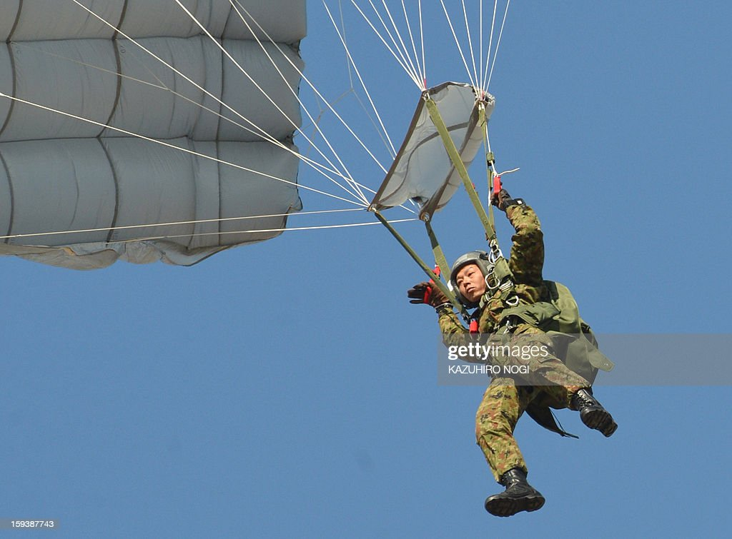 A member of the Japanese Self Defense Forces ground troops parachutes down from a military transport aircraft during a new year drill in Narashino, suburban Tokyo on January 13, 2013. A total of 300 personnel, 20 aircraft and 33 vehicles took part in the open exercise at the defense force's Narashino training ground.