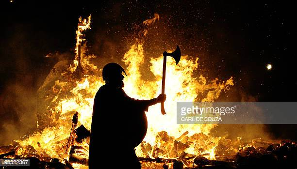 A member of the Jarl viking squad is silhoutted by a burning viking longship during the annual Up Helly Aa Festival Lerwick Shetland Islands January...