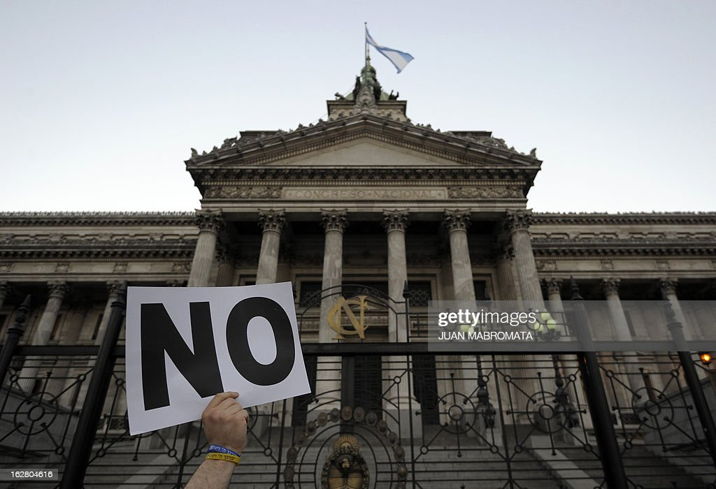 A member of the Jewish community holds a sign outside the Congress building in Buenos Aires on February 27, 2013, while legislatives discuss the possibility of an agreement with Iran to establish a truth commission over a terrorist attack that took place in 1994. Eight Iranian nationals are still wanted in connection with the bombing of the Argentine Israelite Mutual Association (AMIA is Spanish), which left 85 dead and 300 wounded. AFP PHOTO / Juan Mabromata