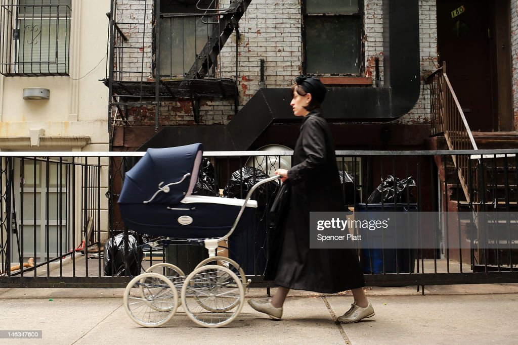 A member of the Jewish Orthodox community walks with her child down a street in a Brooklyn neighborhood on June 14 2012 in New York City According to...