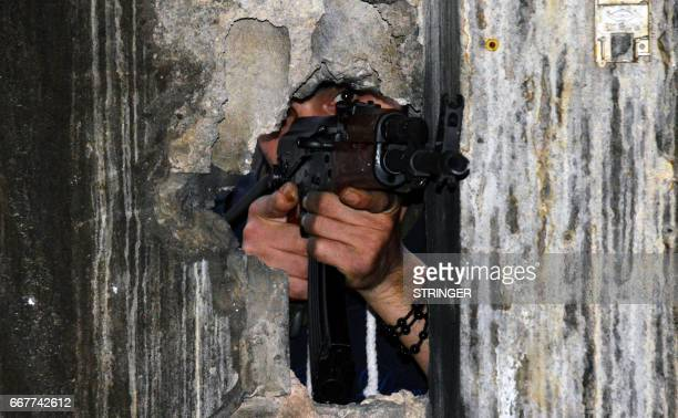 TOPSHOT A member of the joint Palestinian security takes position through a hole in a wall with a kalashnikov assault rifle in Ain alHilweh camp...