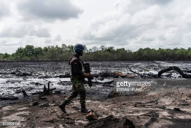 A member of the Joint Task Force Operation Delta Safe walks through an abandoned site of an illegal oil refinery on April 19 2017 in the Niger Delta...
