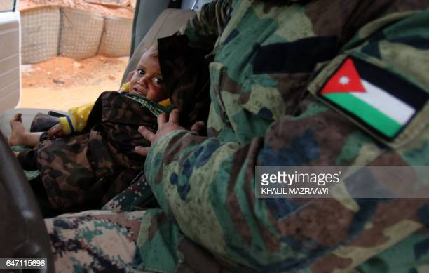A member of the Jordanian armed forces transports a toddler from the informal Rukban camp which lies in noman'sland off the border between Syria and...