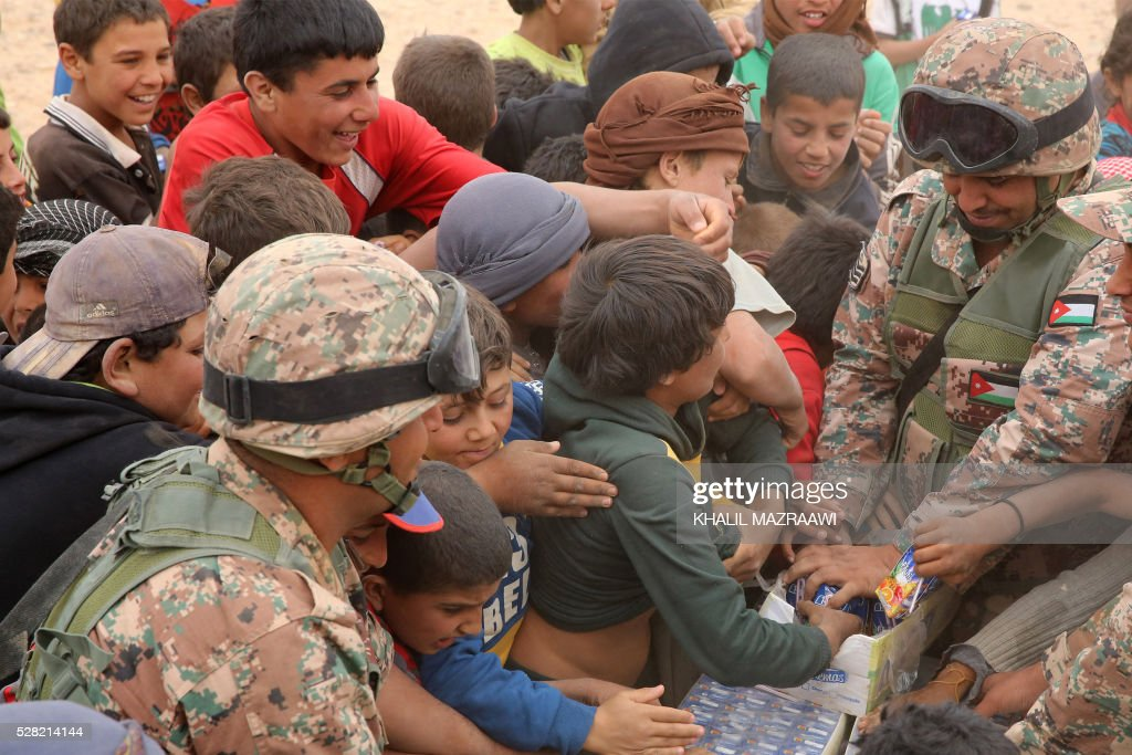 A member of the Jordanian army distributes drinks to newly arrived Syrian refugees waiting to cross to the Jordanian side of the Hadalat border crossing, a military zone east of the capital Amman, after arriving from Syria on May 4, 2016. According to the Jordanian Commander of the Border Guards Brigadier Saber Al-Mahayreh, around 5000 Syrians fleeing from recent attacks on the northern Syrian city of Aleppo are trying to cross into Jordan in search of safety, most of whom are exhausted and desperately in need of help and medical treatment. MAZRAAWI
