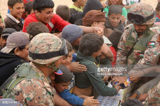 A member of the Jordanian army distributes drinks to newly arrived Syrian refugees waiting to cross to the Jordanian side of the Hadalat border...