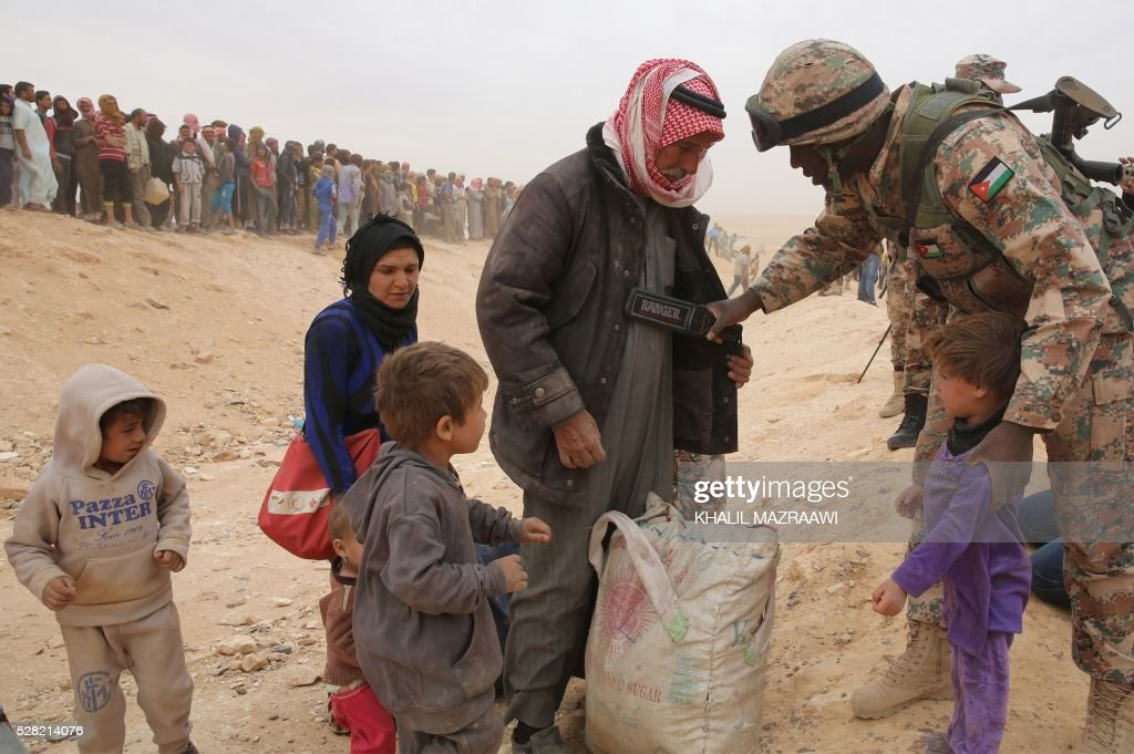 A member of the Jordanian army scans newly arrived Syrian refugees as they wait to cross to the Jordanian side of the Hadalat border crossing, a military zone east of the capital Amman, after arriving from Syria on May 4, 2016. According to the Jordanian Commander of the Border Guards Brigadier Saber Al-Mahayreh, around 5000 Syrians fleeing from recent attacks on the northern Syrian city of Aleppo are trying to cross into Jordan in search of safety, most of whom are exhausted and desperately in need of help and medical treatment. MAZRAAWI