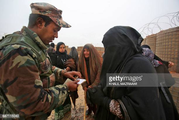 A member of the Jordanian security forces checks identification cards of Syrian refugees from the makeshift Rukban camp which lies in noman'sland off...