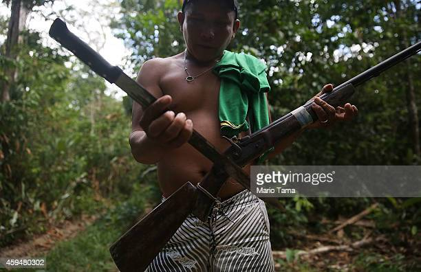 KA'APOR INDIGENOUS RESERVE BRAZIL NOVEMBER 23 A member of the Ka'apor indigenous tribe inspects a rifle and machete confiscated from a man suspected...