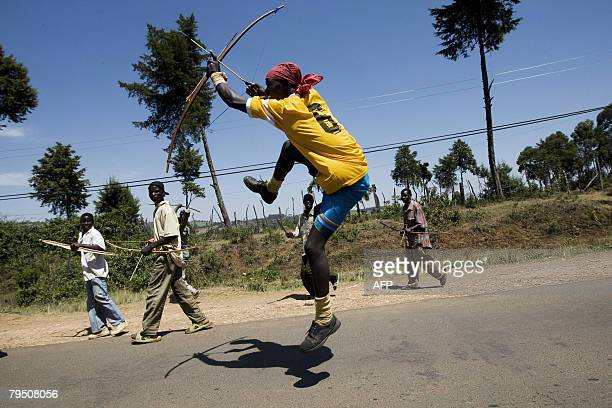 A member of the Kalenjin tribe jumps in the air as he and others carry bows and arrows on a road leading to the western Kenyan town of Chebilat on...
