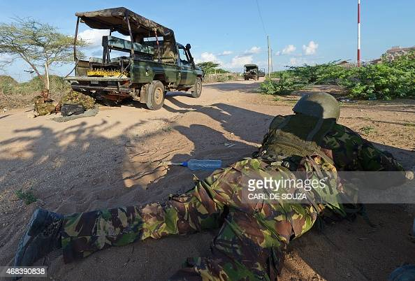 A member of the Kenya Defence Forces takes cover before they ended a siege by gunmen in the university on April 2 2015 in the northeastern town of...