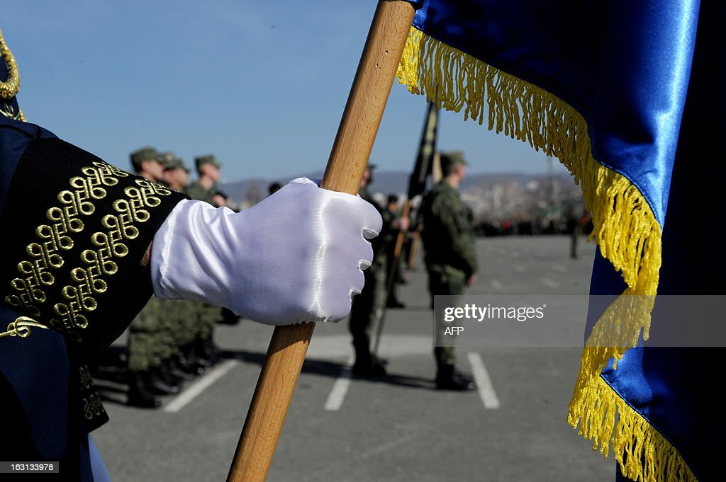 A member of the Kosovo Security Force (KSF) holds a Kosovo flag during a ceremony in Pristina on March 5, 2013 marking the 15th anniversary of the killing of Kosovo Liberation Army (KLA) commander Adem Jashari. Jashari was among 45 members of his family killed by Serb security forces in the vilage of Prekaz some 40 kms west of the Kosovo capital Pristina, sparking a full-blown rebel insurgency.
