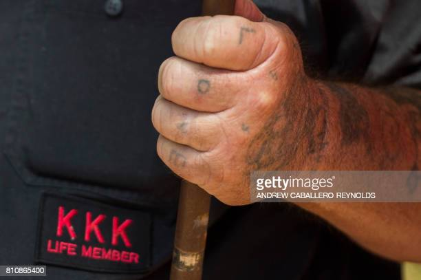 A member of the Ku Klux Klan with the word 'Love' tattooed on his fingers holds a flag during a rally calling for the protection of Southern...