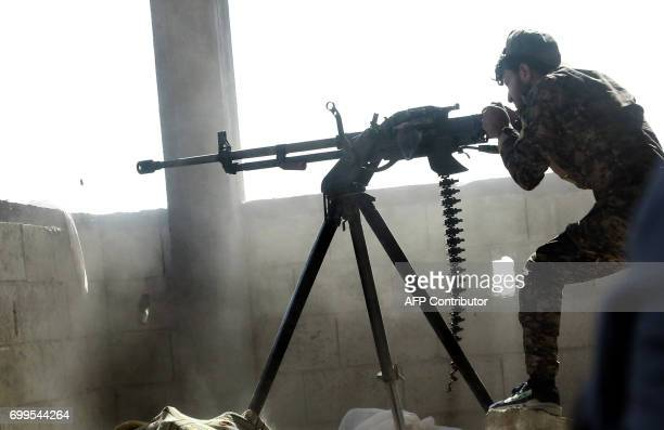 TOPSHOT A member of the Kurdish People's Protection Units fires a machine gun in the Syrian city of Raqa's eastern alSinaa district on June 21 during...