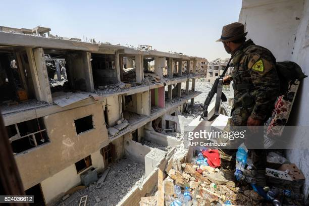 A member of the Kurdish People's Protection Units moves through destroyed buildings in Raqa on July 28 2017 The Syrian Democratic Forces a USbacked...