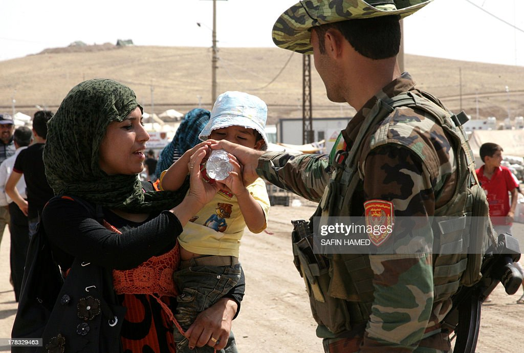 A member of the Kurdish Peshmerga battalions helps a boy drink from a bottle at the Quru Gusik refugee camp, 20 kilometres east of Arbil, the capital of the autonomous Kurdish region of northern Iraq, on August 29, 2013. Over 1.9 million Syrians in total have fled their homeland, mostly to neighbouring Arab states and Turkey, since the revolt against President Bashar al-Assad erupted in 2011.