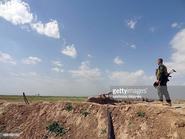 A member of the Kurdish Peshmerga forces monitors the surrounding area following clashes with Islamic State group jihadists during a large operation...