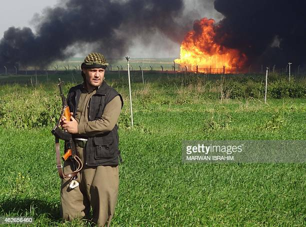 A member of the Kurdish Peshmerga forces walks at the Khubbaz oil field some 25 km west of the northern city of Kirkuk as smoke billows in the...