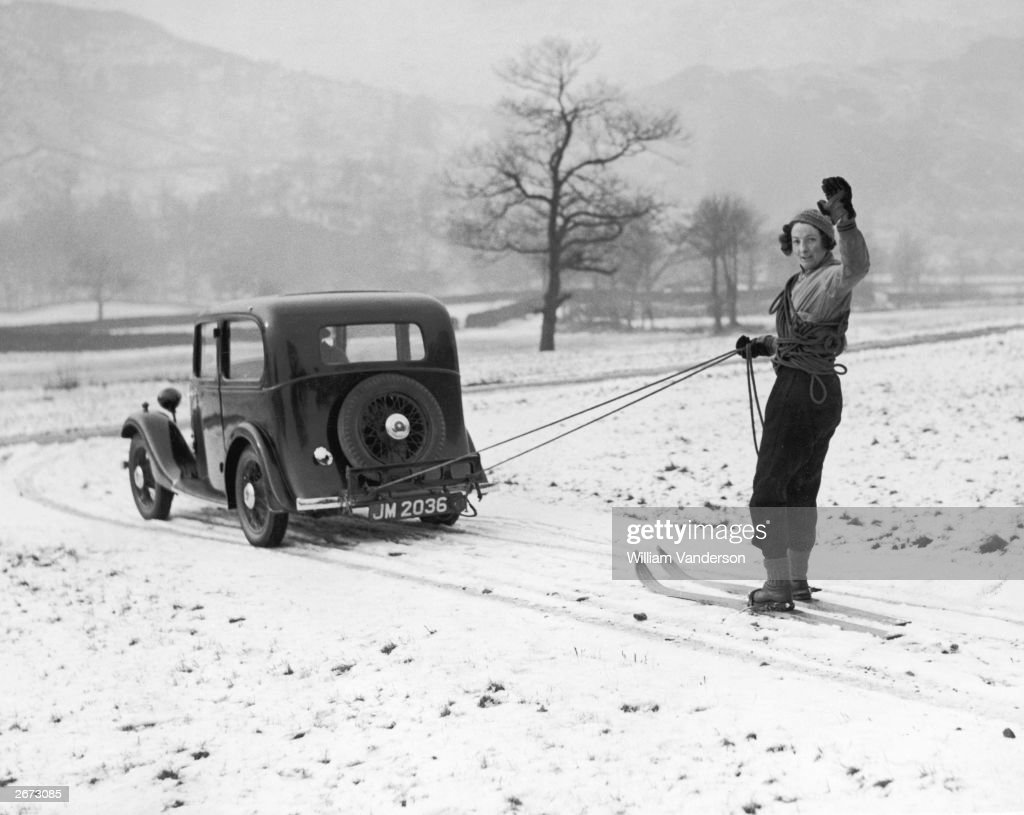 A member of the Lake District Ski Club is pulled along by a Standard Nine saloon car at Ambleside