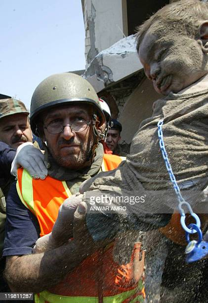 A member of the Lebanese Civil Defence unit shows a dead child to the press after pulling it out of the rubble of a destroyed building in the...