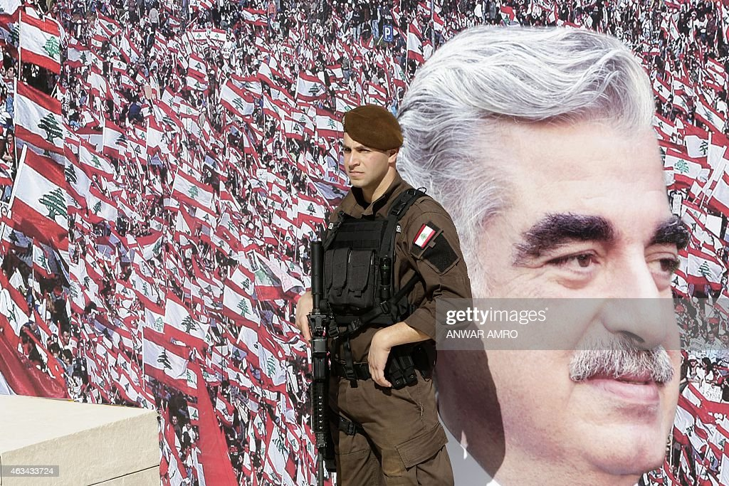 A member of the Lebanese security forces stands guard in front of a billboard bearing a portrait of slain former Lebanese prime minister Rafik Hariri during a ceremony to mark the tenth anniversary of his assassination on February 14, 2015, in downtown Beirut. Lebanese paid their respects to the late former prime minister, a decade after his assassination in a massive and shocking suicide bombing that destabilised the fragile country. AFP PHOTO / ANWAR AMRO