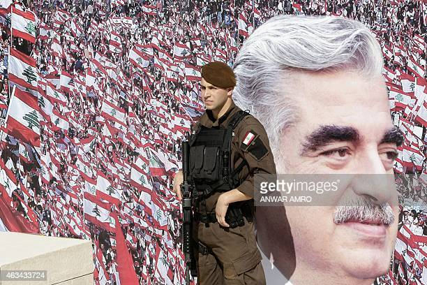 A member of the Lebanese security forces stands guard in front of a billboard bearing a portrait of slain former Lebanese prime minister Rafik Hariri...