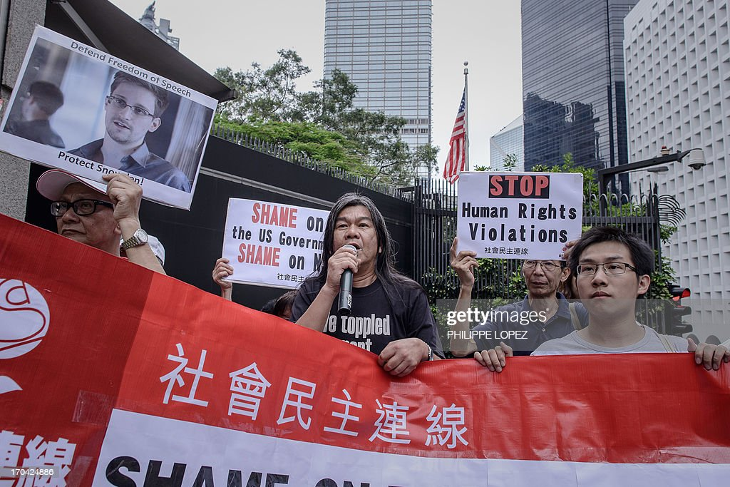 Member of the Legislative Council of Hong Kong, Leung Kwok-hung (C), leads protesters as they shout slogans in support of former US spy Edward Snowden outside the US consulate in Hong Kong on June 13, 2013. Snowden broke his silence on June 12, vowing to fight any bid to extradite him from Hong Kong and accusing Washington's cyber-troops of prying into hundreds of thousands of targets globally including many in China. AFP PHOTO / Philippe Lopez